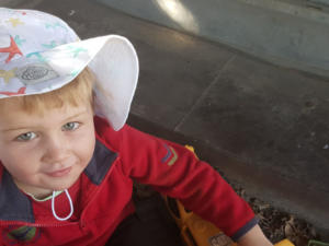 Baby boy in red shirt and hat.