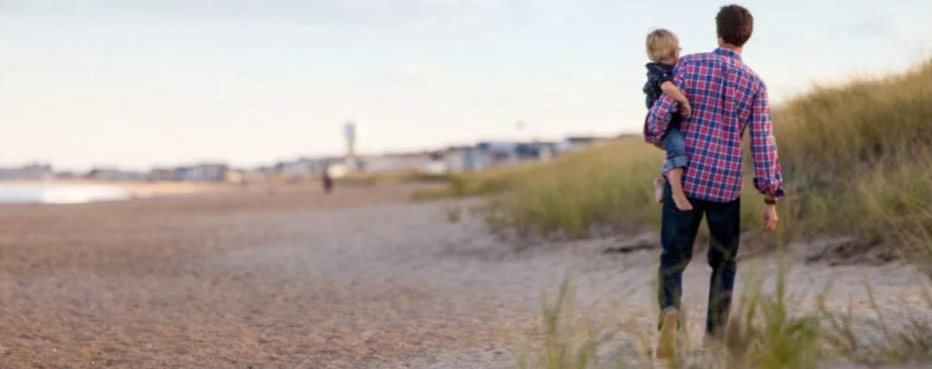 Father walking with boy on hip on beach.
